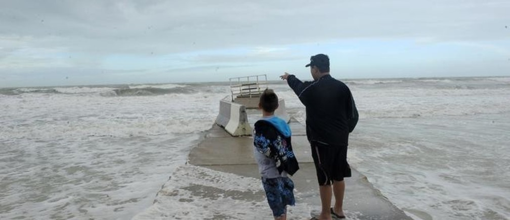 Mike Cook, of Bradenton, and his son Justin, 7, walk out to check out the waves on the Gulf of Mexico as storm surge and high winds associated with Tropical Storm Debby batter Bradenton Beach, Florida, June 25, 2012. The National Hurricane Center expects Debby to make landfall on Thursday in the Florida Panhandle as a tropical storm, but warns that forecasts remain uncertain. REUTERS/Brian Blanco  (UNITED STATES - Tags: ENVIRONMENT DISASTER)