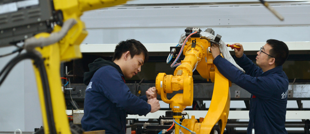 Men manufacture robotic arms at a factory in Huzhou, China