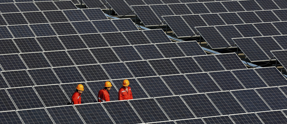 Workers walk among newly installed solar panels at a solar power plant in Zhouquan township of Tongxiang, Zhejiang province December 18, 2014