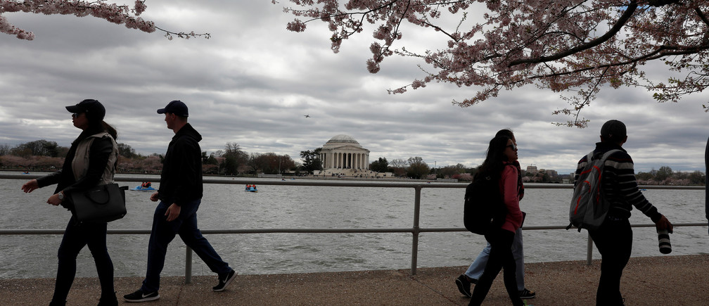 People walk under cherry blossoms near the Tidal Basin in Washington, D.C., U.S., April 1, 2017.  REUTERS/Aaron P. Bernstein - RTX33O3B