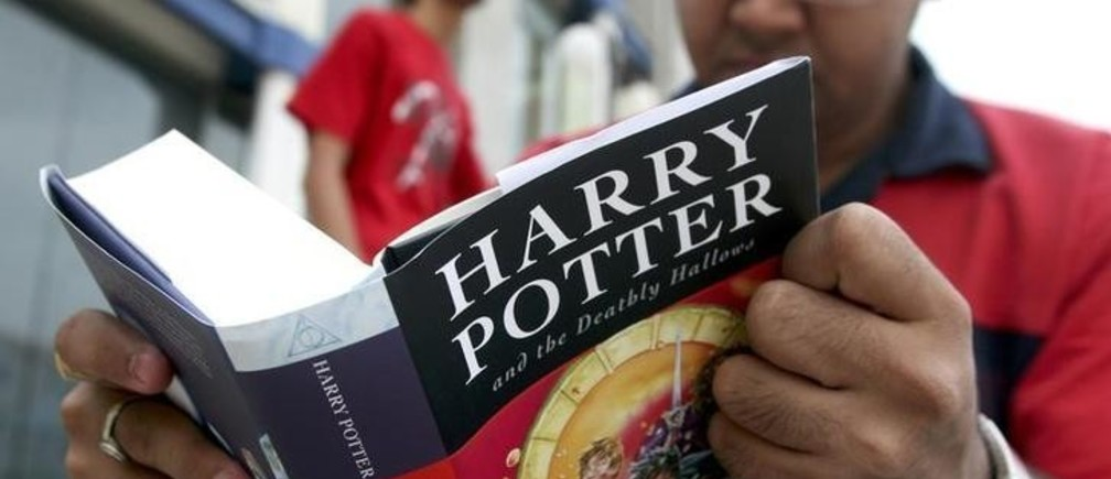"A fan reads the new ""Harry Potter and the Deathly Hallows"" by J.K. Rowling as he sits outside a bookstore in the western Indian city of Ahmedabad July 21, 2007. Harry Potter fans poured into book stores around the world on Saturday to get hold of the seventh and final volume in the series and discover the secret of the boy wizard's fate. REUTERS/Amit Dave (INDIA)"