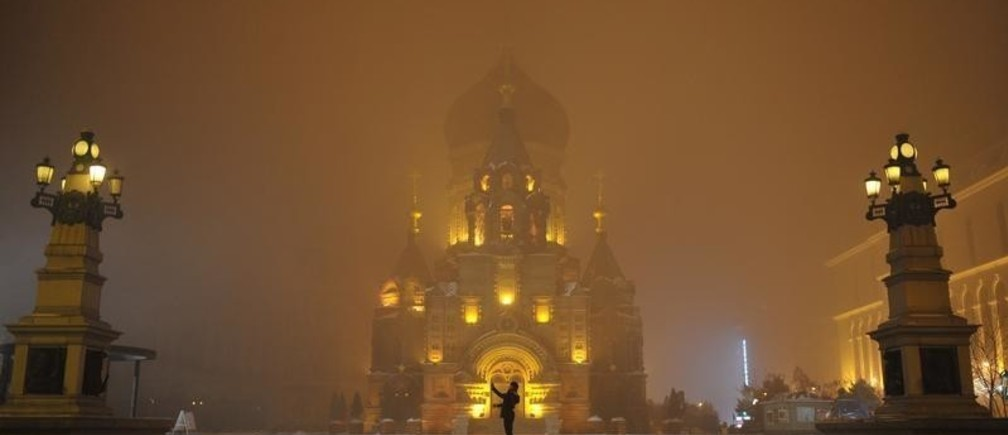 A person takes pictures in smog at the square in front of a church in Harbin, Heilongjiang province, November 10, 2015. Picture taken November 10, 2015. REUTERS/Stringer CHINA OUT. NO COMMERCIAL OR EDITORIAL SALES IN CHINA      TPX IMAGES OF THE DAY      - RTS6F3Y