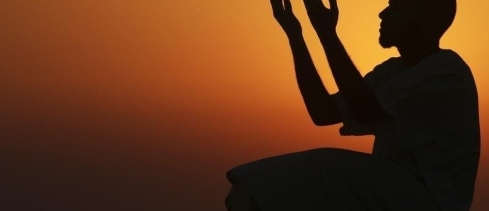 A man raises his hands to pray near the sea at sunset after a day of fasting in the holy month of Ramadan in Benghazi July 24, 2012. Picture taken July 24, 2012. REUTERS/Esam Al-Fetori (LIBYA - Tags: RELIGION SOCIETY TPX IMAGES OF THE DAY) - RTR35A9L