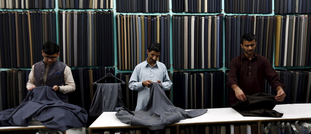 Tailors work under lights powered by a generator in a shop in Islamabad April 9, 2015. After ordering summer dress code and switching off air-conditioners in offices, the Pakistani government has reintroduced a plan to beat the energy crisis in Islamabad - shops and restaurants must close earlier. REUTERS/Caren Firouz