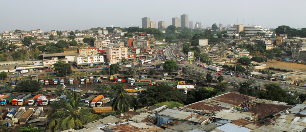 Buildings in Abidjan's business district on the horizon, with informal housing in front, in the Ivory Coast.