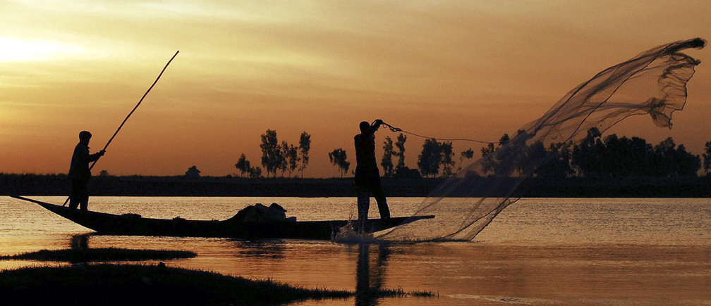 """A Bozo fisherman casts his net from a pirogue in front of Saaya village in the Niger river inland delta February 7, 2007. The Bozo, a West African ethnic group located predominantly along the Niger River in Mali, are famous for their fishing skills and are locally occasionally referred to as the """"masters of the river"""". Picture taken on February 7, 2007. REUTERS/Florin Iorganda   (MALI) - RTR1M4GU"""