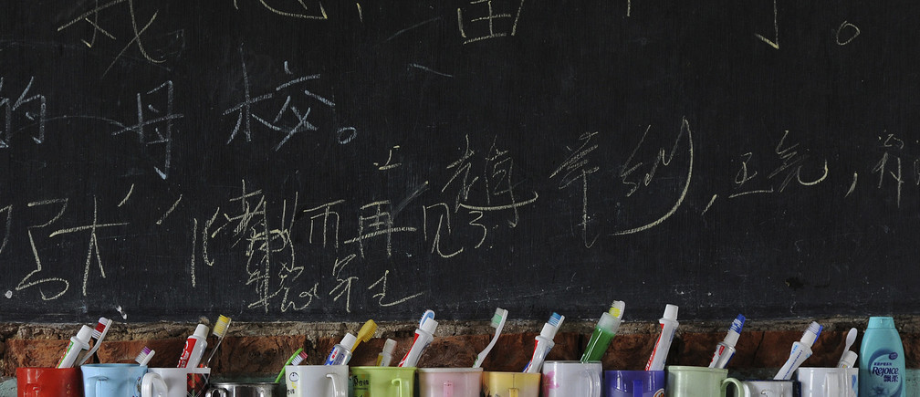 "Toothbrushes and toothpaste are seen in cups in front of a blackboard bearing Chinese characters which read: ""My heart stays. My alma mater, teachers, goodbye"" which were left by the previous students inside their dormitory at Yangguang primary school in Feidong county, Anhui province August 31, 2011. Founded in 2006, the school was the first civilian-run boarding school for ""leftover children"" whose parents left their hometown to earn a living. It currently has 10 teachers and a total of 303 students from the age of 3 to 14, local media reported. Picture taken August 31, 2011. REUTERS/Stringer (CHINA - Tags: EDUCATION SOCIETY TPX IMAGES OF THE DAY) - GM1E7910Z8601"