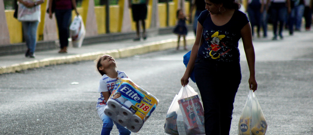 A Venezuelan child carries a pack of toilet paper next to a woman as they cross the Colombian-Venezuelan border over the Simon Bolivar international bridge, after shopping and taking advantage of the temporary border opening in San Antonio del Tachira, Venezuela, July 10, 2016 REUTERS/Carlos Eduardo Ramirez - RTSHA1T