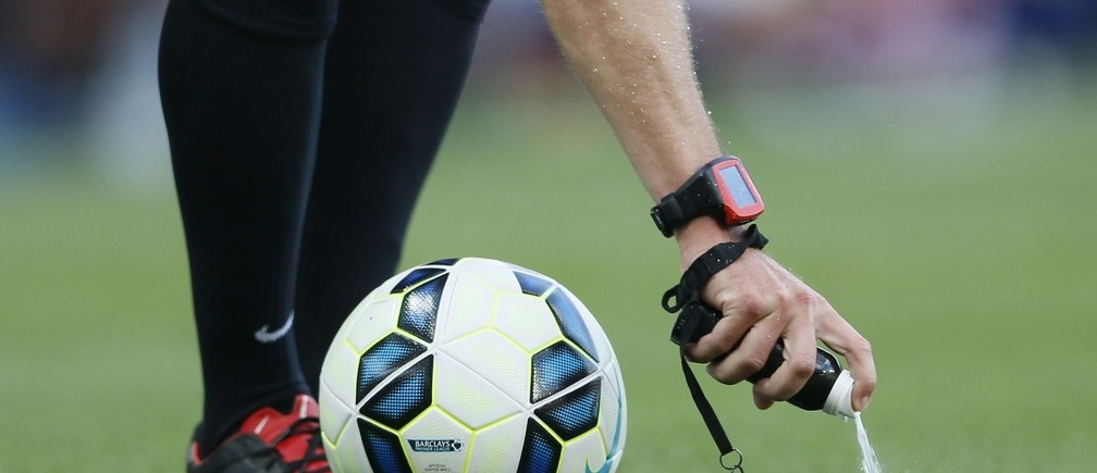 Match referee Jon Moss uses vanishing spray to mark the boundary of the ball during a free kick in the English Premier League soccer match between Arsenal and Crystal Palace at the Emirates stadium in London August 16, 2014.