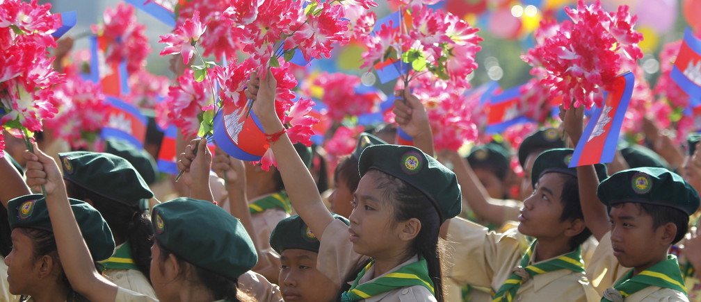 Students hold up plastic flowers and Cambodian flags during celebrations marking the country's independence from France in central Phnom Penh.