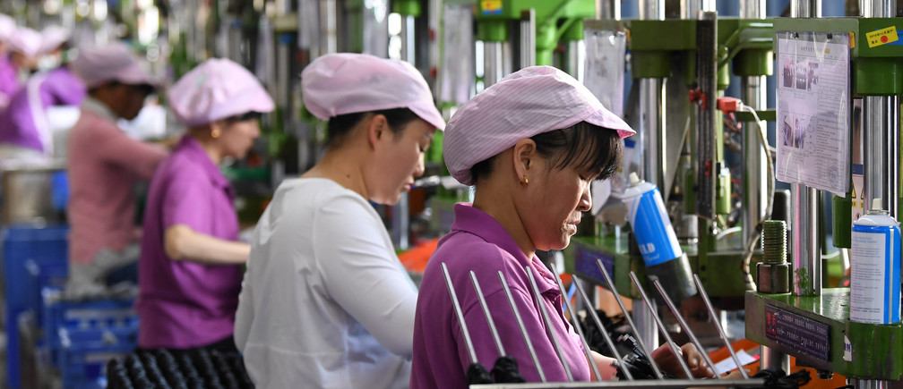 Women work on a data cable production line at a factory in Xinyu, Jiangxi province, China April 8, 2019. Picture taken April 8, 2019. REUTERS/Stringer  ATTENTION EDITORS - THIS IMAGE WAS PROVIDED BY A THIRD PARTY. CHINA OUT. - RC1B26DAD3C0