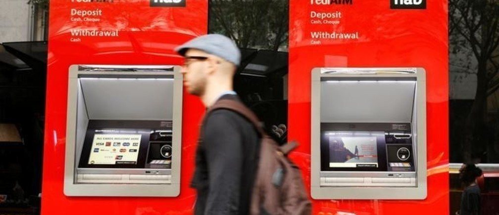 A man walks past ATM machines at a National Australia Bank branch in Sydney, Australia April 20, 2018. REUTERS/Edgar Su