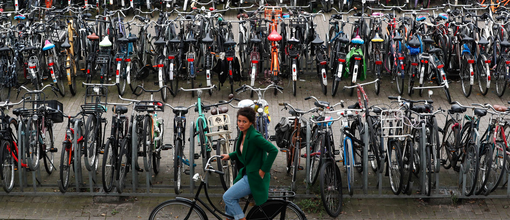 A cyclist rides past a big bike parking near Amsterdam Central Station in Amsterdam, Netherlands September 26, 2017.   REUTERS/Yves Herman - RC19B3DBAF10