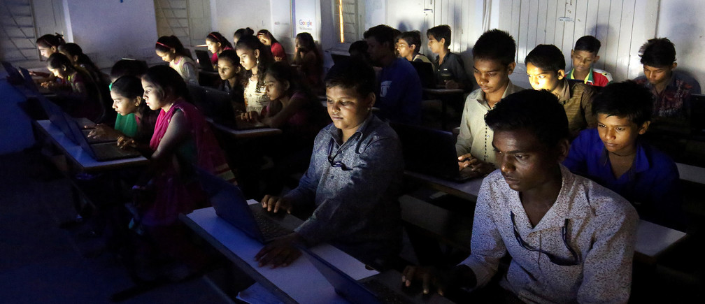 Slum students study on their laptops inside an E-classroom at a government run school in Ahmedabad, India, July 25, 2018. REUTERS/Amit Dave - RC17EC5B6130