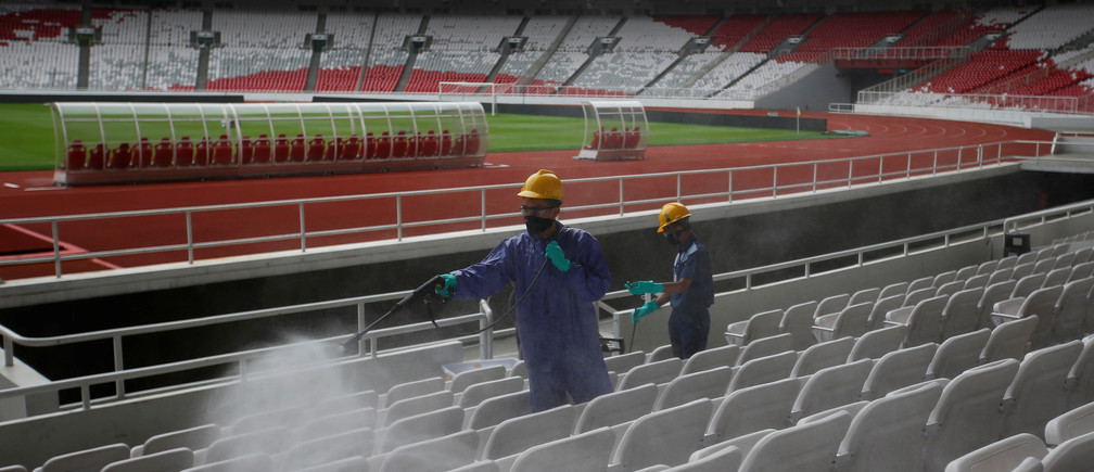 Workers spray disinfectant inside Gelora Bung Karno main stadium after Indonesia's capital began a two-week emergency period to prevent the spread of coronavirus disease (COVID-19) in Jakarta, Indonesia, March 26, 2020. REUTERS/Willy Kurniawan - RC2HRF9VQRQE