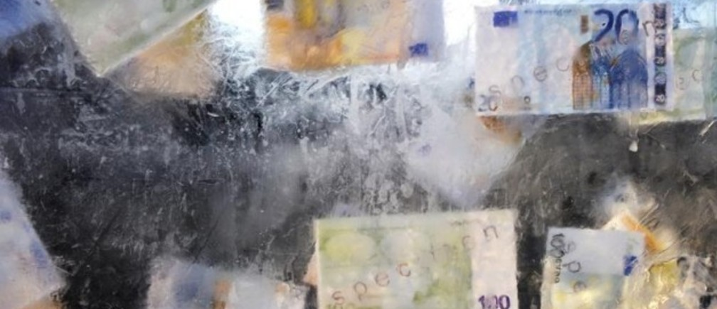 Image: Fake euro banknotes are seen in a block of ice symbolizing austerity measures, during a demonstration by trade unions and workers in central Brussels February 21, 2013. REUTERS/Eric Vidal