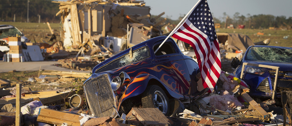 A U.S. flag sticks out the window of a damaged hot rod car in a suburban area after a tornado near Vilonia, Arkansas April 28, 2014. On a second day of ferocious storms that have claimed at least 19 lives in the southern United States, a tornado tore through the Mississippi town of Tupelo on Monday causing widespread destruction to homes and businesses, according to witnesses and local emergency officials. Most of the deaths from the violent storms occurred on Sunday when tornadoes tossed cars like toys in Arkansas and other states. REUTERS/Carlo Allegri (UNITED STATES - Tags: DISASTER ENVIRONMENT TPX IMAGES OF THE DAY) - GM1EA4T0R6Z01
