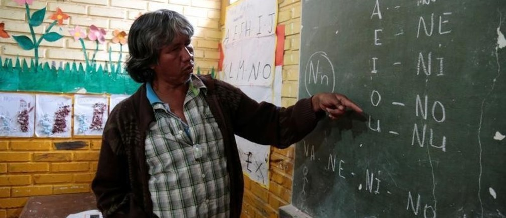 Teacher Blas Duarte shows letters in the Maka language at a school used by children of the Paraguayan ethnic group Maka, in Mariano Roque Alonso, Paraguay July 18, 2019. Picture taken July 18, 2019.  REUTERS/Jorge Adorno - RC127104F750