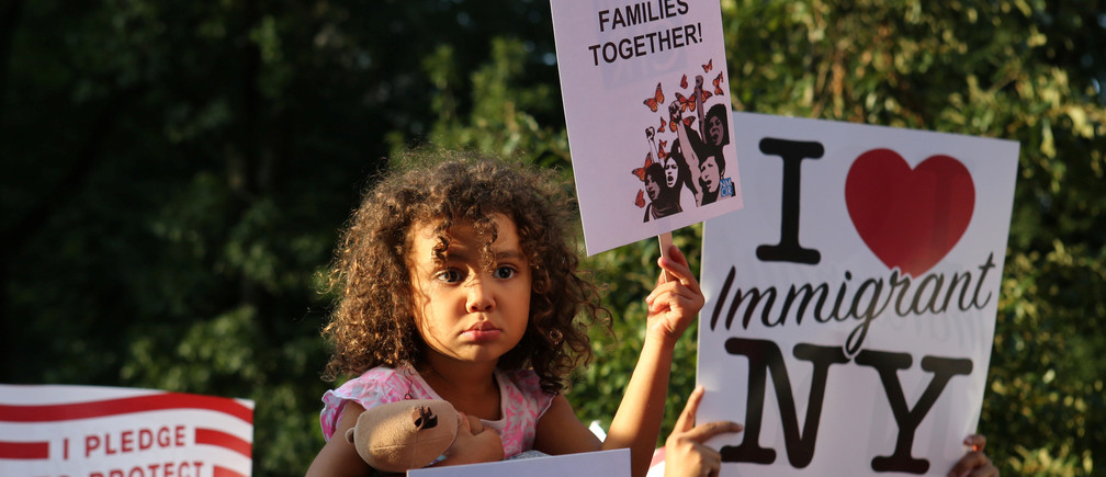 """A girl sitting on the shoulders of her father holds a sign reading """"Keep Families Together"""" at a protest against U.S. President Donald Trump's proposed end of the DACA program that protects immigrant children from deportation in New York City, U.S., August 30, 2017. REUTERS/Joe Penney - RC1F207E1690"""