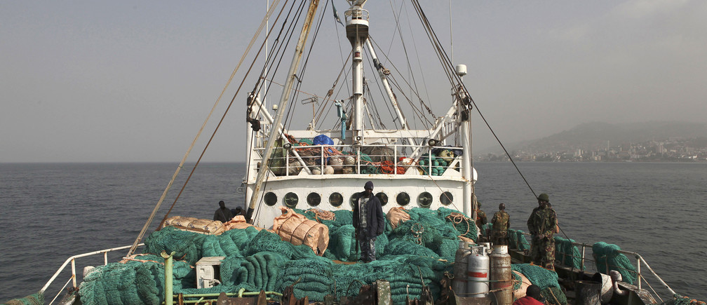 Sierra Leonean security forces supervise the crew on board a vessel apprehended for alleged illegal fishing activities in 2012.