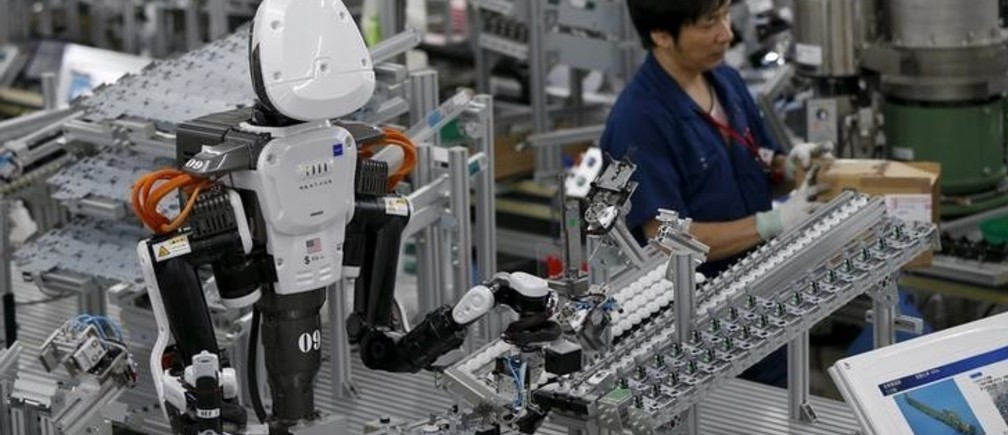 A humanoid robot works side by side with employees in the assembly line at a factory of Glory Ltd., a manufacturer of automatic change dispensers, in Kazo, north of Tokyo, Japan, July 1, 2015. Japanese firms are ramping up spending on robotics and automation, responding at last to premier Shinzo Abe's efforts to stimulate the economy and end two decades of stagnation and deflation. Picture taken July 1, 2015. REUTERS/Issei Kato