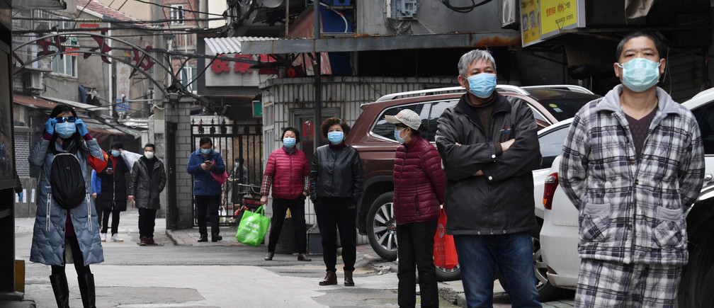 Residents line up to collect vegetables purchased through group orders at a residential area in Wuhan, the epicentre of the novel coronavirus outbreak, Hubei province, China March 5, 2020.  REUTERS/Stringer  CHINA OUT. - RC2PDF9U1064