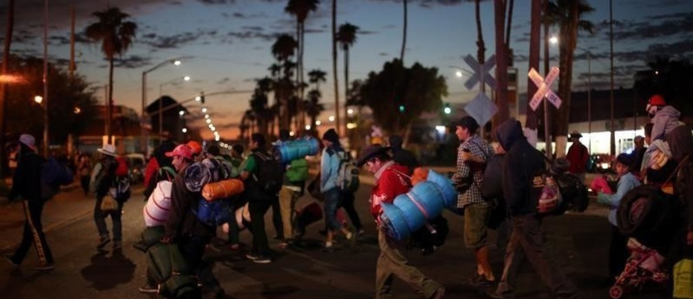 Migrants, part of a caravan of thousands traveling from Central America en route to the United States, make their way to Tijuana from Mexicali, Mexico, November 20, 2018. REUTERS/Hannah McKay - RC1C01C5EEF0