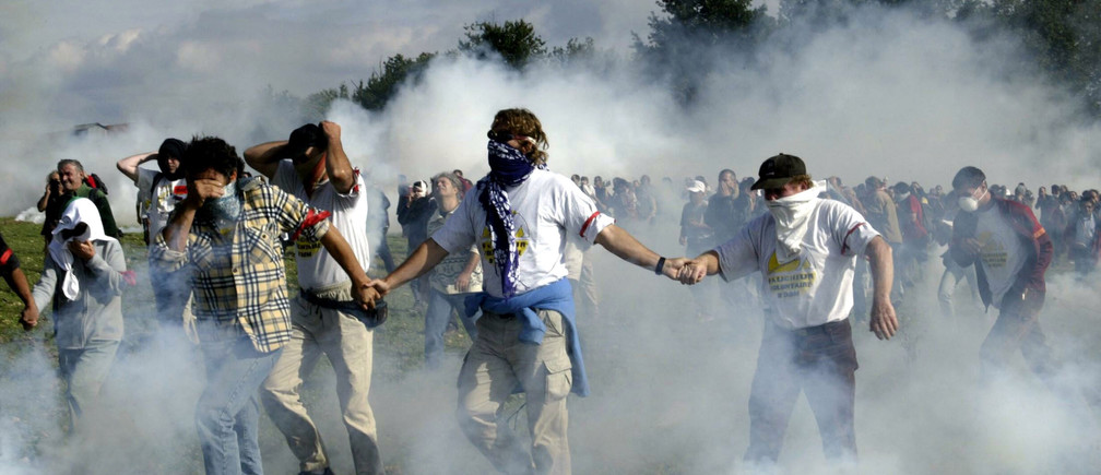 Anti GMO protesters clash with French police during a demonstration in a field in the small village of Valddevienne near Poitiers, France September 25, 2004. - PBEAHUOFTCF
