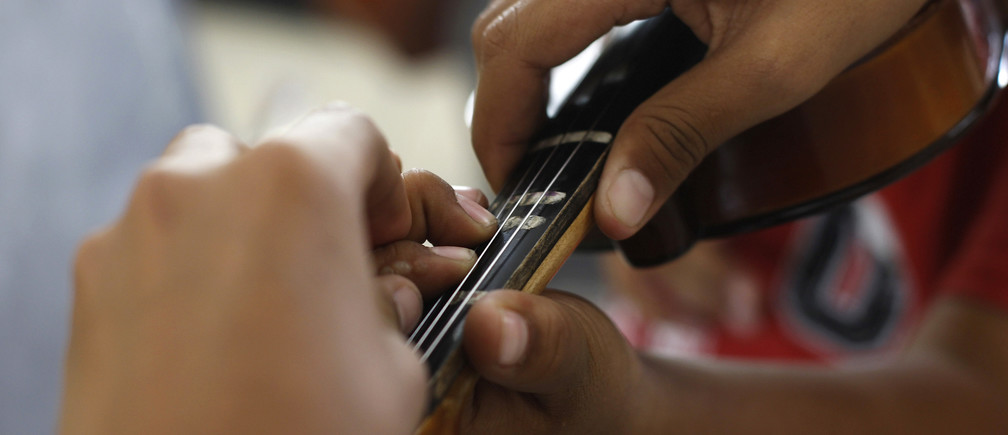 A student helps another student place fingers on the fingerboard of a violin during music lessons at their school in Ciudad Juarez, October 14, 2010. In one of the world's deadliest cities, where drug gangs murder a dozen people a day, a former heroin addict is changing lives with violins and trumpets rather than assault rifles. Alma Rosa Gonzalez is helping poor children learn classical music and give them an outlet that might stop them falling prey to the gangsters who are terrorizing this city of about 1.5 million on the Texas border. Picture taken October 14, 2010. To match feature MEXICO-DRUGS/ORCHESTRA  REUTERS/Tomas Bravo (MEXICO - Tags: SOCIETY CIVIL UNREST EDUCATION) - RTXVH2S