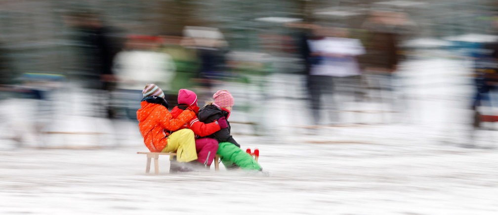 Children ride a sledge after heavy snowfall in Berlin, Germany January 8, 2017. REUTERS/Hannibal Hanschke - RC1146B4F4C0