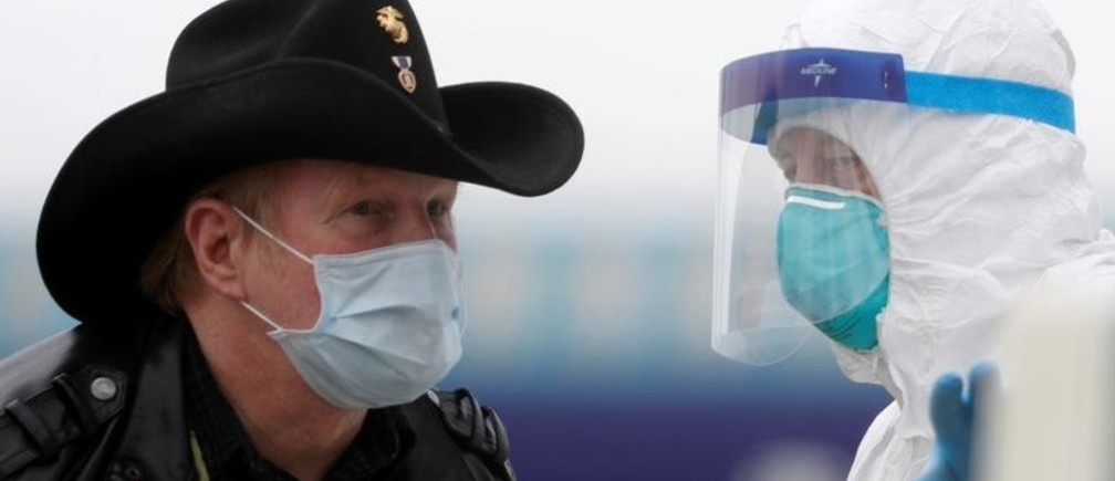 A worker in protective gear directs a masked passenger from the cruise ship Grand Princess on the tarmac at Oakland International Airport as authorities continue debarkation from the ship after 21 people on board have tested positive for the COVID-19 coronavirus in Oakland, California, U.S. March 10, 2020. REUTERS/Stephen Lam     TPX IMAGES OF THE DAY - RC29HF9D9QU6