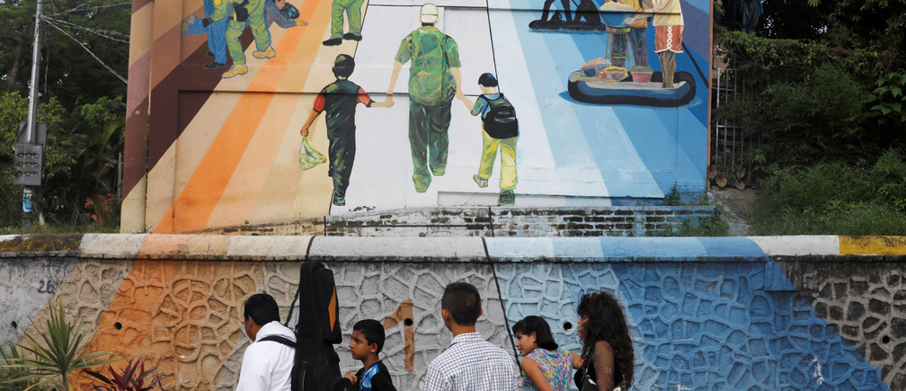 A family walks by a mural depicting the journey of central american migrants to the US in San Salvador, El Salvador, June 21, 2018. REUTERS/Jose Cabezas - RC1F3DC136C0