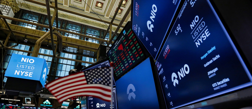 An American flag is seen among logos for Chinese electric vehicle start-up NIO Inc., on the trading floor of the New York Stock Exchange (NYSE) as NIO stock begins trading during the company's initial public offering (IPO) at the NYSE in New York, U.S., September 12, 2018. REUTERS/Brendan McDermid - RC1AD89AA640