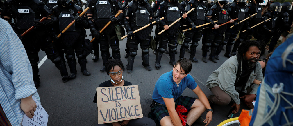 Protesters sit with their backs to riot policemen during nationwide unrest following the death in Minneapolis police custody of George Floyd, in Raleigh, North Carolina, U.S. May 31, 2020. Picture taken May 31, 2020. REUTERS/Jonathan Drake - RC270H91Y6CW