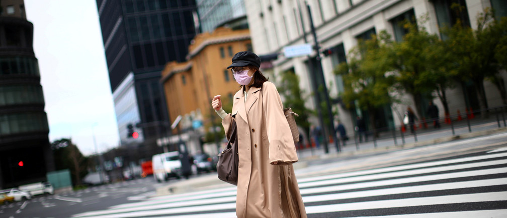 A woman, wearing protective face masks following an outbreak of the coronavirus disease (COVID-19), walks on a street in Tokyo, Japan March 9, 2020. REUTERS/Edgard Garrido - RC27GF9L0MB9