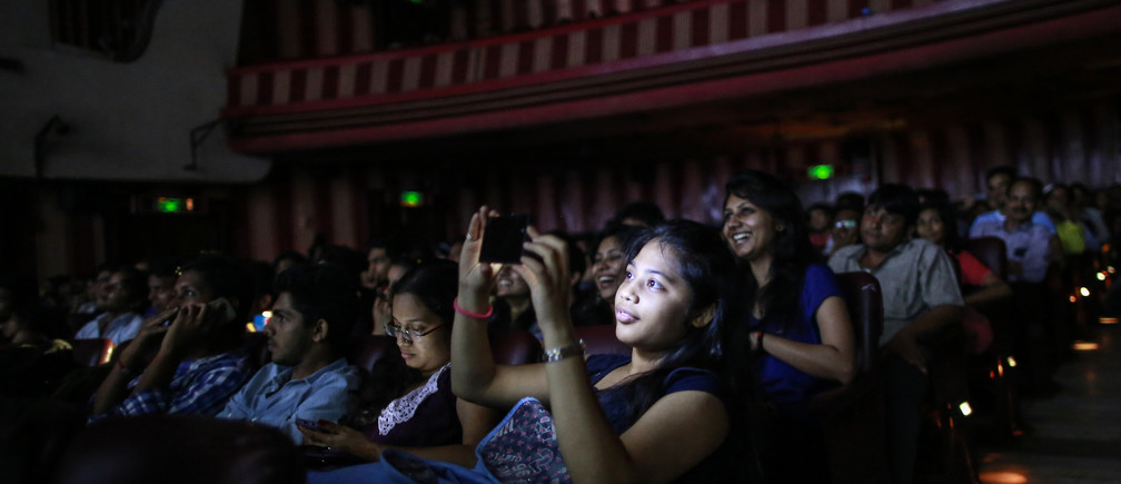 "A cinema goer takes a picture as others watch Bollywood movie ""Dilwale Dulhania Le Jayenge"" (The Big Hearted Will Take the Bride), starring actor Shah Rukh Khan, inside Maratha Mandir theatre in Mumbai December 12, 2014. The movie, released in October 1995, has set a record of completing 1000 weeks of continuous screening at a cinema, a feat unmatched by any other Bollywood movies. According to Manoj Desai, owner of the theatre, the movie, which is still being screened, enjoys at least 50 to 60 percent occupancy on weekdays and full house on weekends at his theatre."