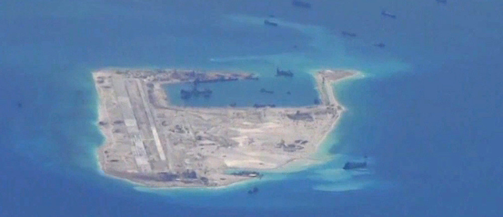 Chinese dredging vessels are purportedly seen in the waters around Fiery Cross Reef in the disputed Spratly Islands in the South China Sea in this still image from video taken by a P-8A Poseidon surveillance aircraft provided by the United States Navy May 21, 2015.