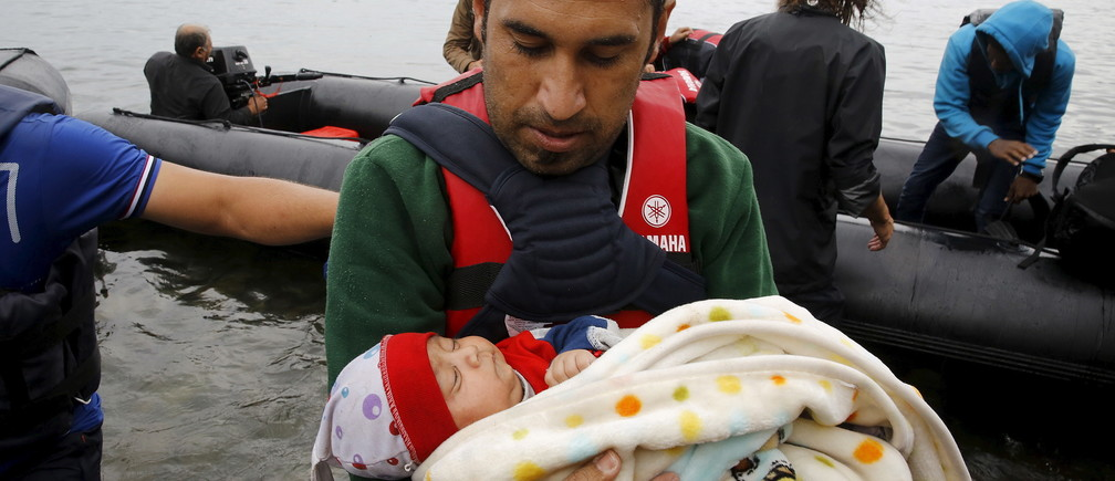 A Syrian refugee carries his baby child off an overcrowded dinghy after crossing part of the Aegean Sea from Turkey to the Greek island of Lesbos.
