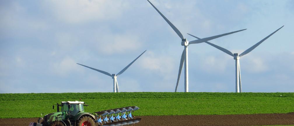 Un agriculteur français conduit un tracteur alors qu'il laboure un champ devant des éoliennes génératrices d'électricité sur un parc éolien à Havrincourt, en France, le 10 novembre 2019.