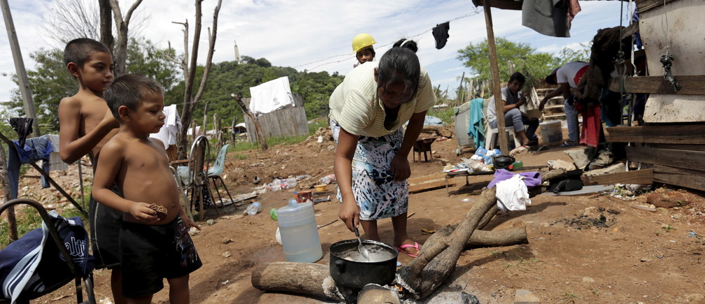 A Paraguayan woman cooks in one of Paraguay's poor neighborhoods in Asuncion, March 31,2015. Paraguay's government announced that the poverty index rose in 2014 over the previous year, a tendency that goes against the government's official goal of improving the standard of living.