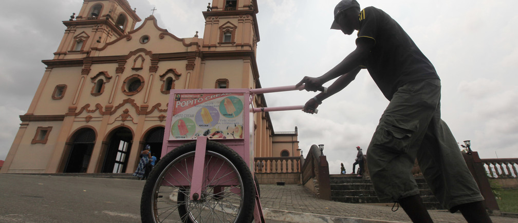 An ice cream seller walks in front of the main Cathedral in Bata January 29, 2012. The majority of the population in Equatorial Guinea is Christian. REUTERS/Amr Abdallah Dalsh