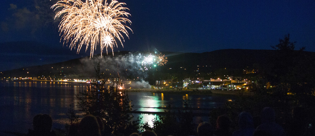 Residents watch fireworks explode over their town following the G7 Summit in the Charlevoix town of La Malbaie, Quebec, Canada, June 9, 2018.  REUTERS/Christinne Muschi - RC1978AF46D0