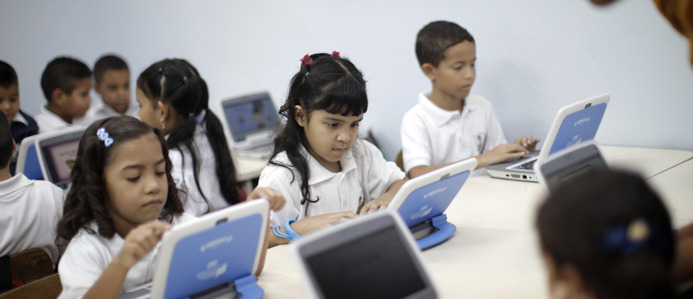 First grade children follow a lesson on their new laptops as part of the Canaima project at a Bolivarian school in Caracas September 23, 2009.