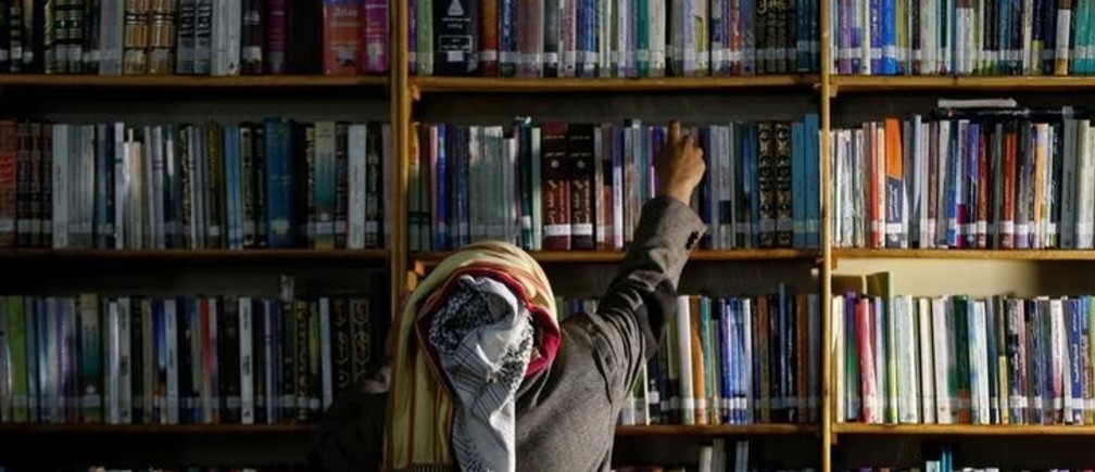 Yemeni author Mohammed al-Qaoud picks a book at a library in Sanaa, Yemen April 18, 2018. Picture taken April 18, 2018. REUTERS/Khaled Abdullah