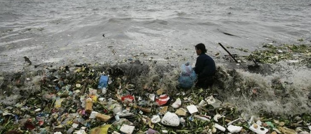 A man collects recyclable plastic materials, washed ashore by waves, which will be sold for 21 pesos ($0.48) in exchange for food in Manila  August 2, 2008. REUTERS/Cheryl Ravelo (PHILIPPINES)
