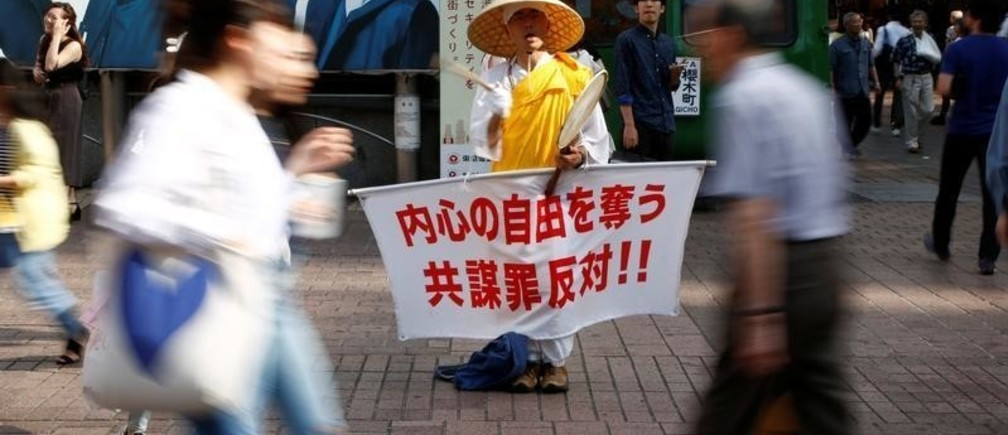 """A monk holds a placard with a slogan against a bill targeting conspiracies to commit terrorism and other serious crimes, in front of Shibuya station in Tokyo, Japan June 9, 2017. The slogan reads, """"Oppose to conspiracy law which deprives freedom in the mind""""."""