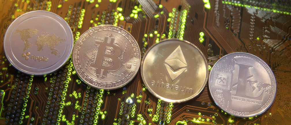 Representations of the Ripple, Bitcoin, Etherum and Litecoin virtual currencies are seen on a PC motherboard in this illustration picture, February 13, 2018. Picture is taken February 13, 2018. REUTERS/Dado Ruvic/Illustration - RC1993E31370