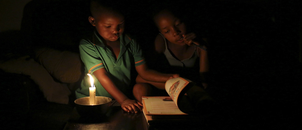 Sinovuyo Bhungane (R), 9, looks on as her studies are interrupted by her cousin Yonga, as she studies using candle light during load shedding in Soweto February 3, 2015