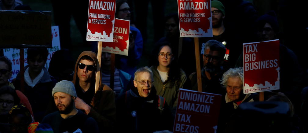 "People cheer as they hold ""Tax Amazon"" signs during a protest in front of the Amazon Spheres to demand that the city of Seattle tax the largest corporations to help fund affordable housing, according to organizers, in Seattle, Washington, U.S., April 10, 2018"