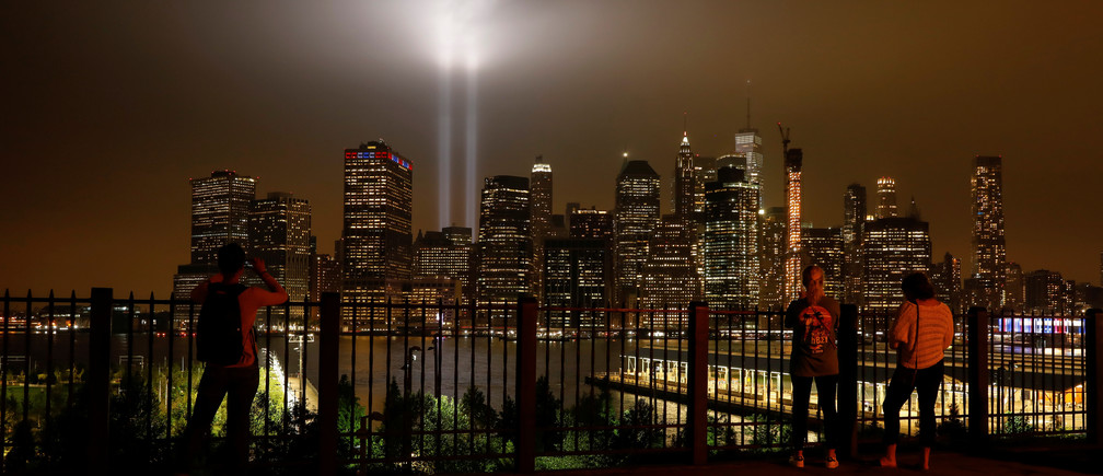 People look at the Tribute in Light installation as it illuminates lower Manhattan as seen from the borough of Brooklyn, marking the 17th anniversary of the 9/11 attacks in New York City, U.S., September 11, 2018. REUTERS/Brendan McDermid